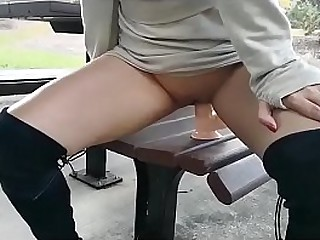 Asian slut getting fucked by a dildo in a park