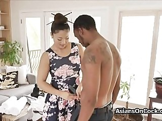 Oiled Asian babe blows a huge black cock during massage